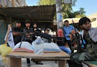 Syrian people stand next to a checkpoint manned by rebels in the northern city of Aleppo. Rebels accused strongman Bashar al-Assad on Tuesday of moving chemical weapons to Syria's borders, a day after his beleaguered regime said it would use its stockpiles if attacked