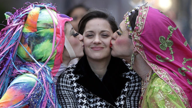 Actress Marion Cotillard, of France, center, the Hasty Pudding Woman of the Year, is kissed by Harvard University theatrical students Renee Rober, left, and Ben Moss, right, as they ride in the back of a convertible during a parade through Harvard Square, in Cambridge, Mass., Thursday, Jan. 31, 2013. The award was presented to Cotillard by Hasty Pudding Theatricals, a theatrical student society at Harvard University. (AP Photo/Steven Senne)