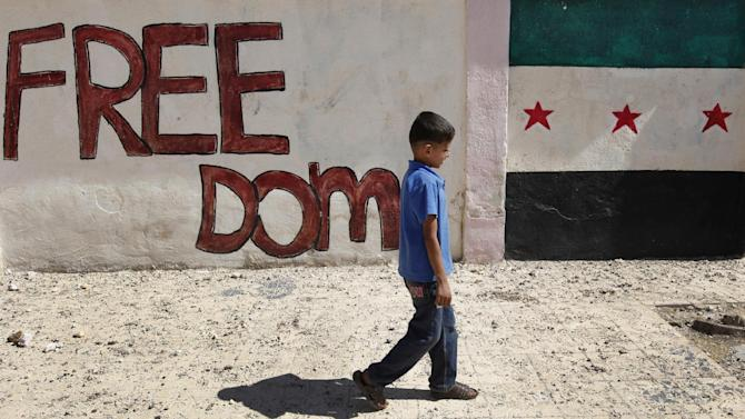 A Syrian boy walks in front of wall painted with colors of the Syrian revolutionary flag, right, in Marea village, on the outskirts of Aleppo, Syria, Sunday Sept. 23, 2012. Syria's bloody 18-month conflict, which activists say has killed nearly 30,000 people, has so far eluded all attempts at international mediation. (AP Photo/Hussein Malla)