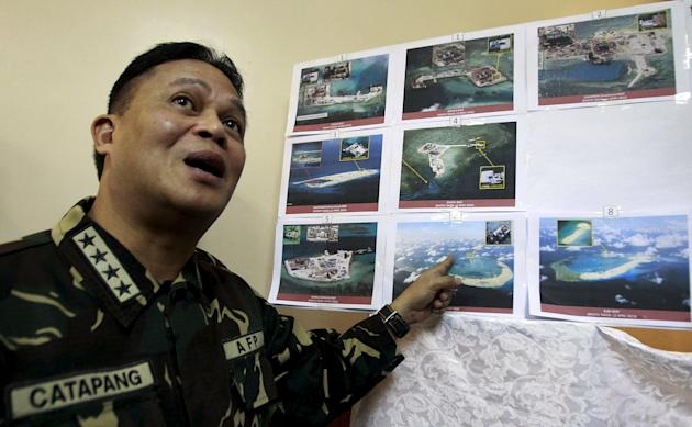 Armed Forces of the Philippines (AFP) Chief of Staff Gregorio Pio Catapang shows some images of the structures being built by China at the disputed islands during a news conference at the AFP headquar