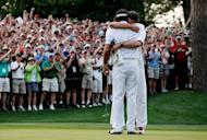 Bubba Watson (R) of the United States hugs his caddie Ted Scott after winning his sudden death playoff on the second playoff hole to win the 2012 Masters Tournament by one stroke at Augusta National Golf Club in Augusta, Georgia