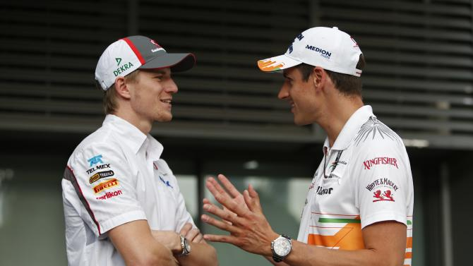 Sauber F1 driver Hulkenberg of Germany talks to compatriot Force India driver Sutil before the drivers pre-race news conference ahead of the Singapore F1 Grand Prix