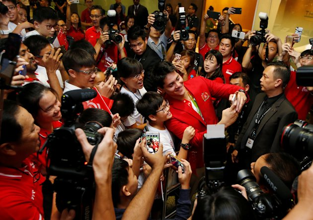 Singapore Olympic gold medallist swimmer Joseph Schooling takes a selfie with fans during a homecoming ceremony at Singapore's Changi Airport August 15, 2016. REUTERS/Edgar Su