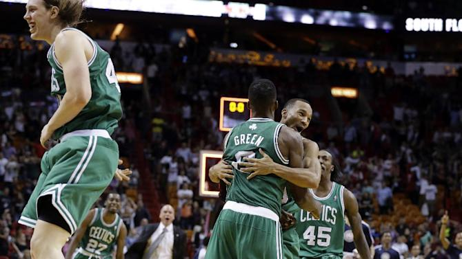 Boston Celtics' Jeff Green is hugged by Avery Bradley after shooting a game-winning three-point basket against the Miami Heat during the second half of an NBA basketball game, Saturday, Nov. 9, 2013, in Miami. The Celtics won 111-110. At left is Celtic's Kelly Olynyk