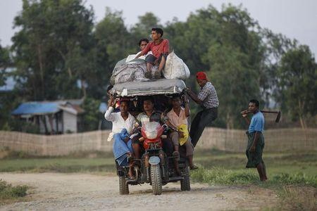 Rohingya Muslims ride a vehicle as they travel outside Sitttwe