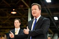 British Prime Minister David Cameron (right) speaks as British Deputy Prime Minister Nick Clegg listens during a visit to the CNH tractor plant in Basildon, Essex, last wee