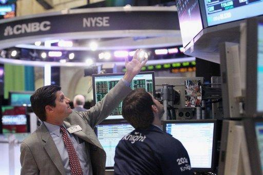 Traders work on the floor of the New York Stock Exchange during afternoon trading on November 19 in New York City. Strong gains by Apple, Facebook and other key tech stocks sent the Nasdaq exchange higher Monday while the Dow and S&P 500 sagged.