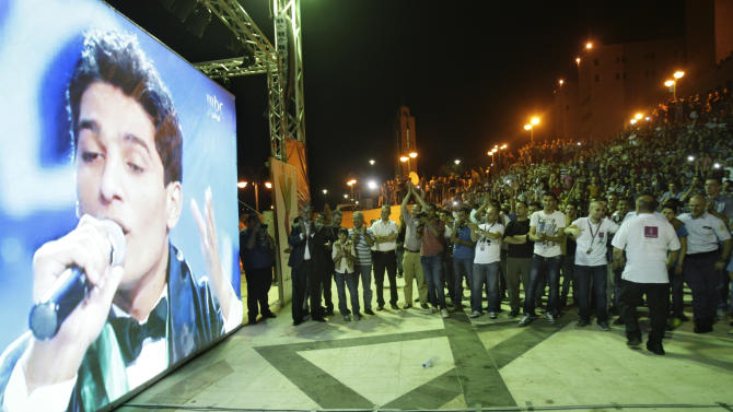 "Palestinians watch the performance of Palestinian singer Mohammed Assaf, a contestant in a regional TV singing contest, on a large screen in the West Bank city of Nablus, Saturday, June 21, 2013. Palestinians relished a rare moment of pride and national unity Saturday after a 23-year-old wedding singer from a refugee camp in the Gaza Strip won ""Arab Idol,"" a regional TV singing contest watched by millions of people. (AP Photo/Nasser Ishtayeh)"
