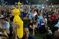 Supporters of the Worker's Party cheer as they wait for results at an assembly center in Singapore, Friday, Sept. 11, 2015. Singaporeans voted Friday in general elections whose results hold no surprises - the ruling People's Action Party will extend its 50-year-rule by another five years. But what will be closely watched is the percentage of votes it garners, which will determine the measure of its popularity as the city-state goes through tough economic times. (AP Photo/Ng Han Guan)