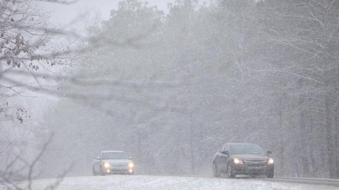 Vehicles move along Hwy 86 in Carrollton, Ala. Thursday, Jan. 17, 2013. A wet blanket of snow covered much of West Alabama Thursday morning.  (AP Photo/The Tuscaloosa News, Dusty Compton)