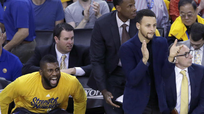 Golden State Warriors center Festus Ezeli, left, and guard Stephen Curry react during the first half in Game 1 of a second-round NBA basketball playoff series against the Portland Trail Blazers in Oakland, Calif., Sunday, May 1, 2016. (AP Photo/Jeff Chiu)