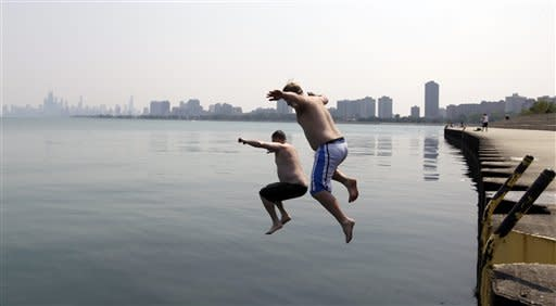 Jason Gerald, left, and Adam Hoffman jump into the Lake Michigan at Montrose Beach Thursday, June 28, 2012 in Chicago. The National Weather Service said the temperature Thursday hit 98 degrees. The last time it hit 100 was 2005. (AP Photo/ Nam Y. Huh)