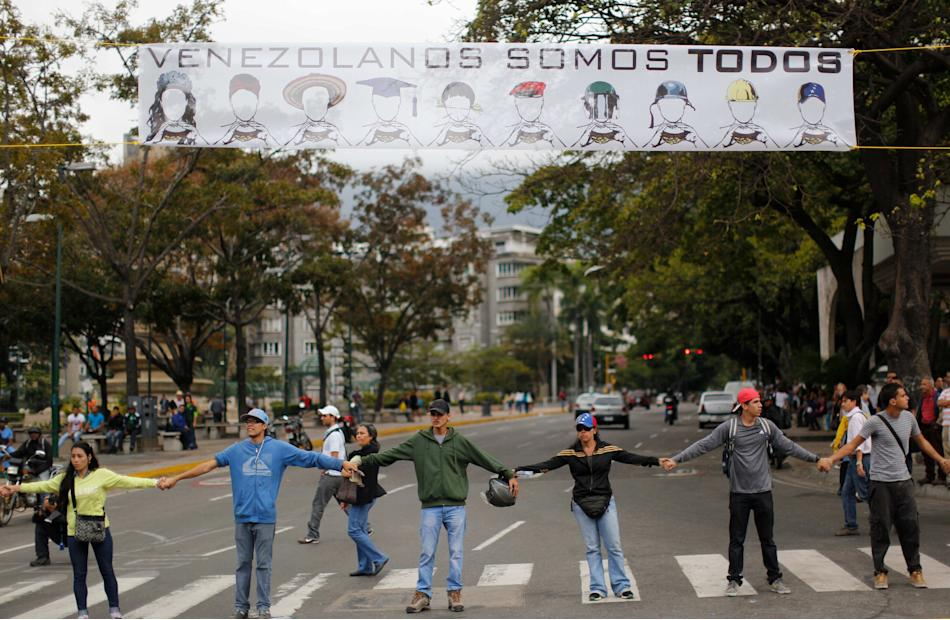 """Demonstrators join hands to block the highway at Altamira neighborhood in Caracas, Venezuela, Monday, Feb. 24, 2014. The banner over their heads reads in Spanish """"We are all Venezuela"""". Traffic has co"""