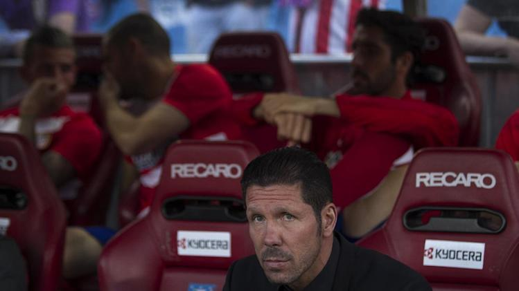 Atletico's coach Diego Simeone sits before a Spanish La Liga soccer match between Atletico de Madrid and Elche at the Vicente Calderon stadium in Madrid, Spain, Friday, April 18, 2014