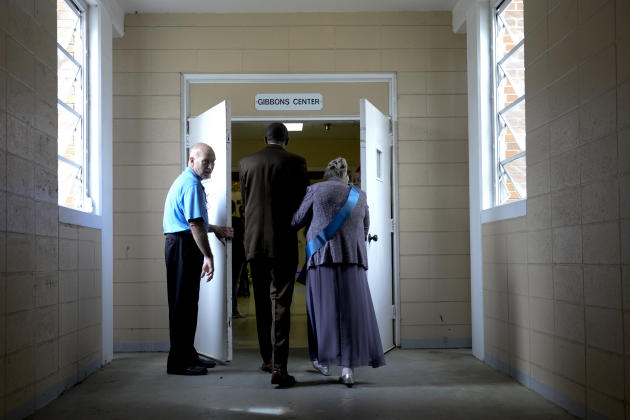 Anna Grantham is escorted through a set of double doors after being introduced as a honor court member during the 15th annual Mrs. Riverview pageant at Riverview health in Savannah, Ga. on Thursday, M