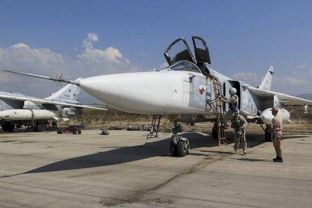 Russia's Defence Ministry handout photo shows pilots of Russian Sukhoi Su-24 fighter jet preparing before flight at Hmeymim air base near Latakia in Syria