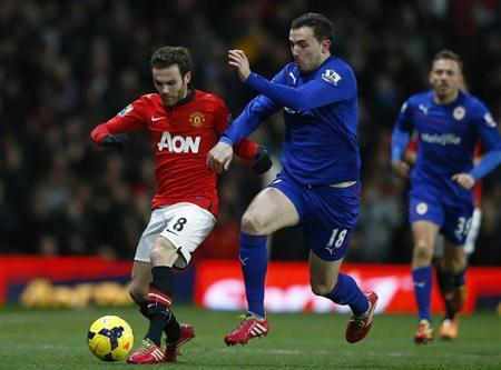 Manchester United's Mata fights for the ball with Cardiff City's Mutch during their English Premier League soccer match in Manchester, northern England