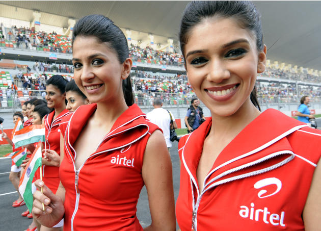 Grand Prix grid girls stand on the track during the drivers' parade in the Formula One Indian Grand Prix at the Buddh International circuit in Greater Noida, southeastern outskirts of New Delhi on Oct