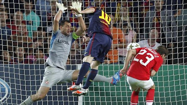 Barcelona's Lionel Messi (C) scores his second goal against Spartak Moscow's Dmitri Kombarov and goalkeeper Andriy Dykan