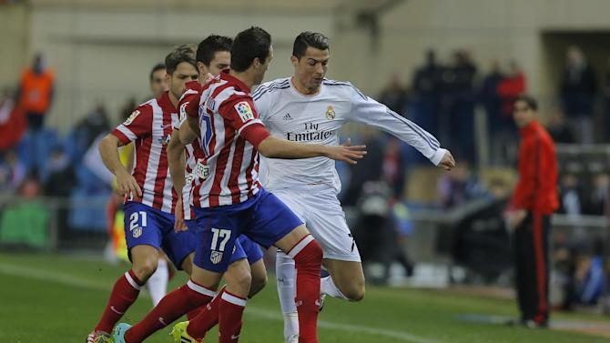 Real's Cristiano Ronaldo, right, in action with Atletico's Javi Manquillo, left, during a semi final, 2nd leg, Copa del Rey soccer match between Atletico de Madrid and Real Madrid at the Vicente Calderon stadium in Madrid, Spain, Tuesday, Feb. 11, 2014