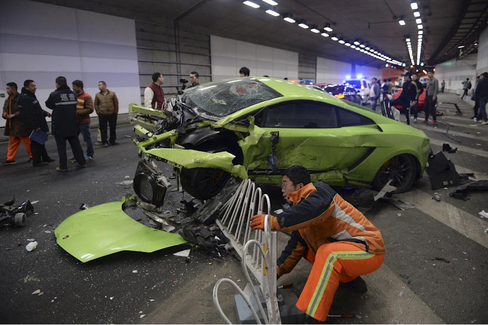 A rescuer tries to remove a part of a broken fence below a damaged Lamborghini after it collided with a Ferrari inside a tunnel in Beijing