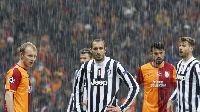Players of Galatasaray and Juventus react as their match is paused for 20 minutes due to heavy snowfall.