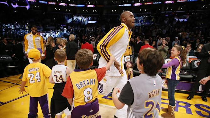 Los Angeles Lakers' Kobe Bryant is greeted by young fans wearing his jersey as he comes onto the floor before the NBA basketball game against the Toronto Raptors  in Los Angeles, Sunday, Dec. 8, 2013. Bryant is expected to make his long-awaited return from a torn left Achilles tendon injury from April 12th