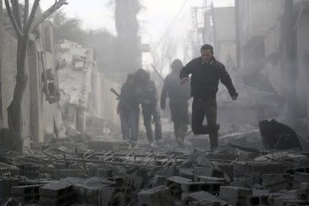 Residents look for survivors after what activists said were air strikes by forces loyal to Assad in Marj Al Sultan, in Damascus suburb of Ghouta