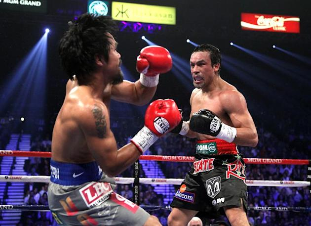 Manny Pacquiao takes a punch from Juan Manuel Marquez during their welterweight fight on December 8, 2012 in Las Vegas