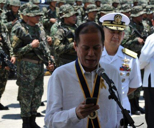 """Philippine President Benigno Aquino looks at his mobile phone after the navy's anniversary celebration at Fort San Felipe, on May 21, 2013. Aquino has announced a $1.8-billion military upgrade to help defend his country's maritime territory against """"bullies"""", amid an ever-worsening dispute with China."""