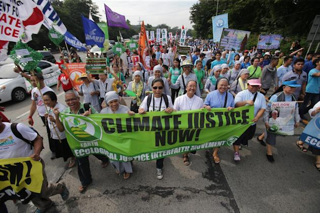 Filipino nuns and priests, along with Catholic groups, lead a march to raise awareness on the dangers of climate change in suburban Quezon city, north of Manila, Philippines as they observe the feast