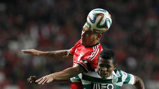 Benfica's Maxi Pereira, top, from Uruguay, out jumps Sporting Lisbon Heldon Ramos, from Cape Verde, during the Portuguese league soccer match between Benfica and Sporting Lisbon at Benfica's Luz stadium, in Lisbon, Tuesday, Feb. 11, 2014