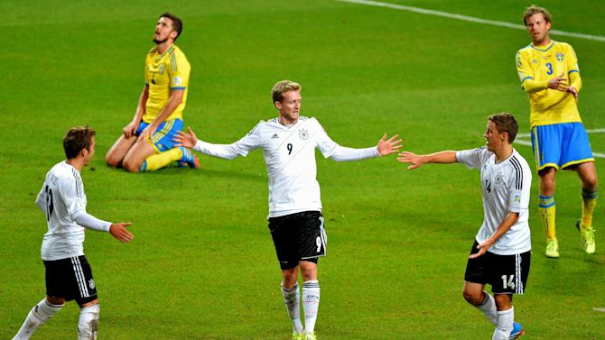 Germany's Andre Schuerrle, center, celebrates scoring with teammates Mario Goetze, left, and Max Kruse while Sweden's Per Nilsson, far left, and Mikael Antonsson look dejected during the 2014 World Cup group C qualifying soccer match between Sweden and Germany at Friends Arena in Stockholm, Sweden, Tuesday, Oct. 15, 2013