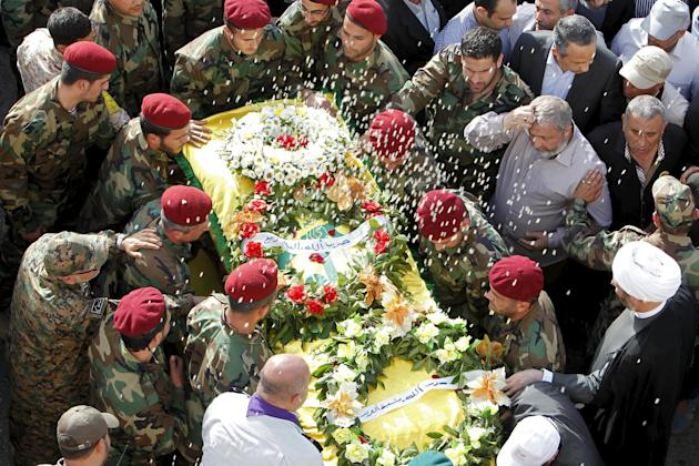 Rice is thrown as Lebanon's Hezbollah members surround the coffin of Hezbollah fighter Adnan Siblini, who was killed while fighting against insurgents in the Qalamoun region, during his funeral in