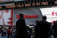 The Times Square news ticker displays a headline on the Facebook stock price on May 18. The suits alleged that Facebook, and Morgan Stanley, Goldman Sachs and other big banks withheld from smaller investors crucial forecasts that pointed to weaker growth for Facebook, while sharing the information with big institutional clients
