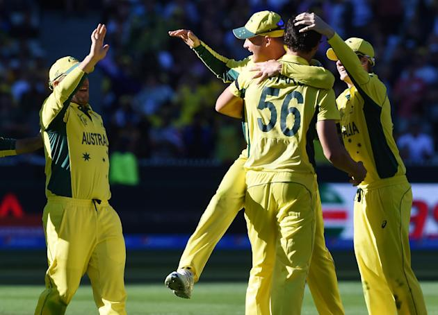Australian players congratulate teammate Mitchell Starc, 56, after taking the wicket of New Zealand wicketkeeper Luke Ronchi for no score during the Cricket World Cup final in Melbourne, Australia, Su