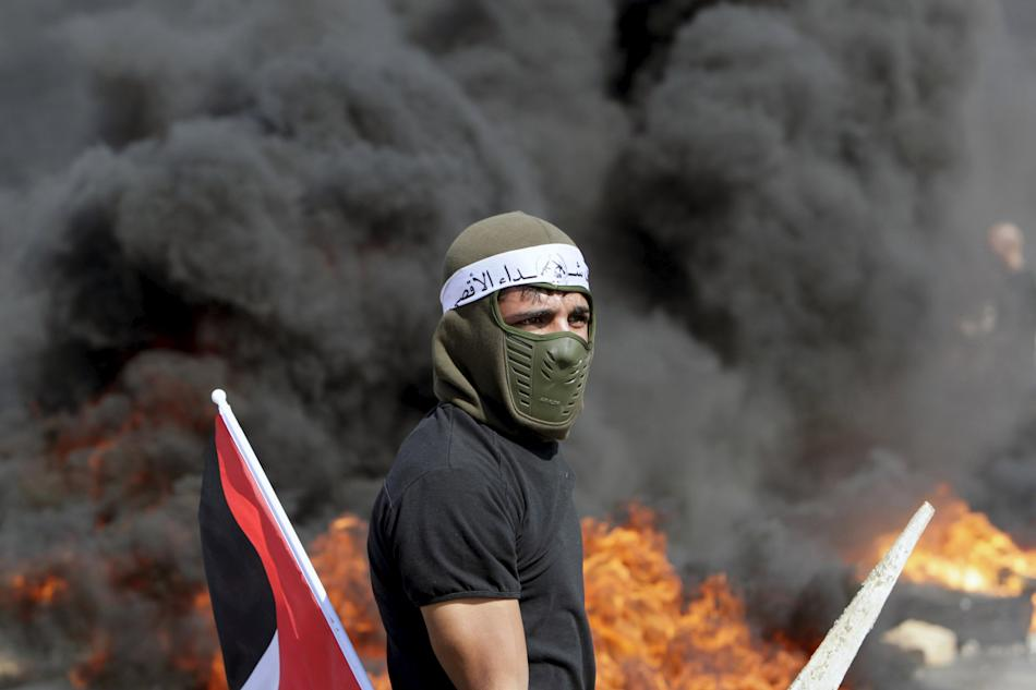 Palestinian protester stands in front of burning tyres during clashes with Israeli troops in the West Bank city of Jenin