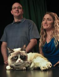 Bryan Bundesen, left and his sister Tabatha Bundesen pose with Grumpy Cat, whose real name is Tardar Sauce, as they prepare for an interview on Friday April 4, 2014 in New York. Tabatha Bundesen says that Grumpy Cat's permanently grumpy-looking face is due to feline dwarfism. (AP Photo/Bebeto Matthews)