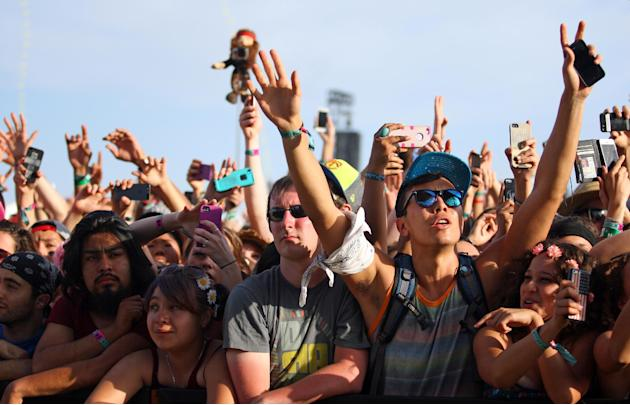 FILE - In this April 19, 2014 file photo, festival goers hold up cameras and phones during the 2014 Coachella Music and Arts Festival in Indio, Calif. You can bring your beach towels and floral headba