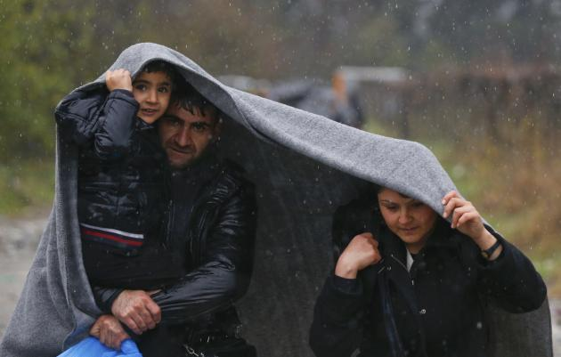 Migrants shield from rain with a blanket as they walk after crossing the border from Greece into Macedonia, near Gevgelija