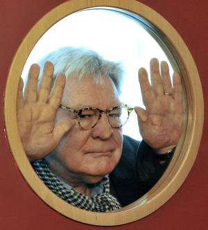 """File - British film director Alan Parker looks through a cinema door window prior to meeting the media in Prague in this Friday, March 28, 2008 file photo.  Alan Parker, the much-lauded British director whose work includes """"Midnight Express,"""" """"Fame"""" and """"Mississippi Burning,"""" is receiving the British Academy Film Awards' highest honor.  The 68-year-old will collect the BAFTA Fellowship at the London ceremony next month. While known for being outspoken, Parker said Tuesday Jan. 22 2013, that he'll be """"gracious and thankful"""" on the big night rather than political.  He tells The Associated Press, """"you always worry, does that mean the end of my career, when you get this kind of thing _ but it's very nice.""""   (AP Photo / CTK, Michal Dolezal, file)  SLOVAKIA OUT"""
