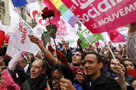 Supporters of France's newly-elected President Francois Hollande react after the early results in the second round vote of the 2012 French presidential elections in Paris