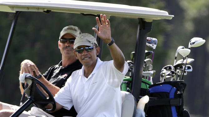 CORRECTS FIRST NAME TO GLENN-President Barack Obama, right, waves to a crowd of onlookers while driving a golf cart with businessman Glenn Hutchins, behind, as they golf at Farm Neck Golf Club in Oak Bluffs, Mass., on the island of Martha's Vineyard, Saturday, Aug. 17, 2013. (AP Photo/Steven Senne)