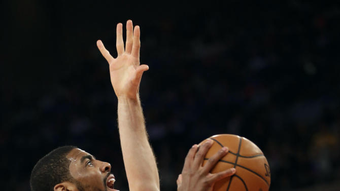 Cleveland Cavaliers' Kyrie Irving, left, puts up a shot past New York Knicks' Andrea Bargnani during the first half of an NBA basketball game, Sunday, Feb. 22, 2015, in New York. (AP Photo/Seth Wenig)