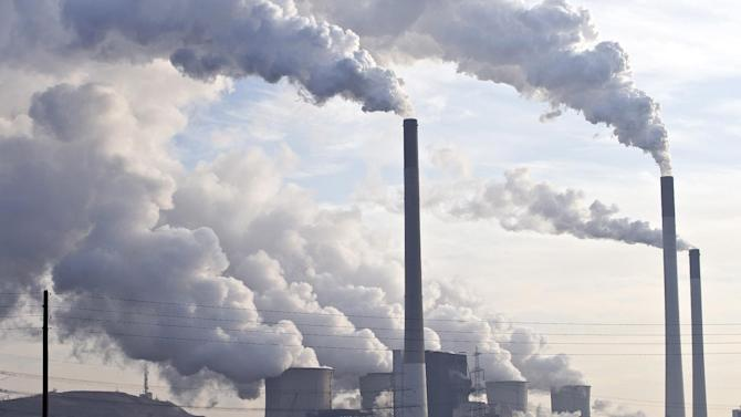 FILE - In this Dec. 16, 2009 file photo, steam and smoke is seen over the coal burning power plant in Gelsenkirchen, Germany. Slowing the buildup of greenhouse gases responsible for warming the planet is one of the biggest challenges the U.S. _ and President Barack Obama _ faces. The impacts of rising global temperatures are widespread and costly: more severe storms, rising seas, species extinctions, and changes in weather patterns that will alter food production and the spread of disease. (AP Photo/Martin Meissner, File)