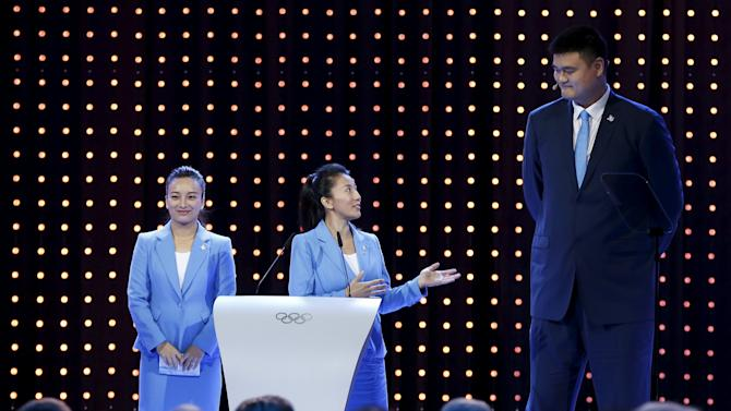 China's speed skater Yang Yang looks towards basketball player Yao Ming, with free skier Li Nina, during Beijing's 2022 Winter Games presentation at the 128th International Olympic Committee Session in Kuala Lumpur, Malaysia