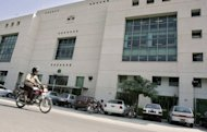 A Pakistani man rides his motorbike in front of the building of the Muslim Commercial Bank (MCB) in Islamabad in 2006. Pakistan's richest man has applied to open Pakistani bank branches in India for the first time since partition 65 years ago, officials said Wednesday
