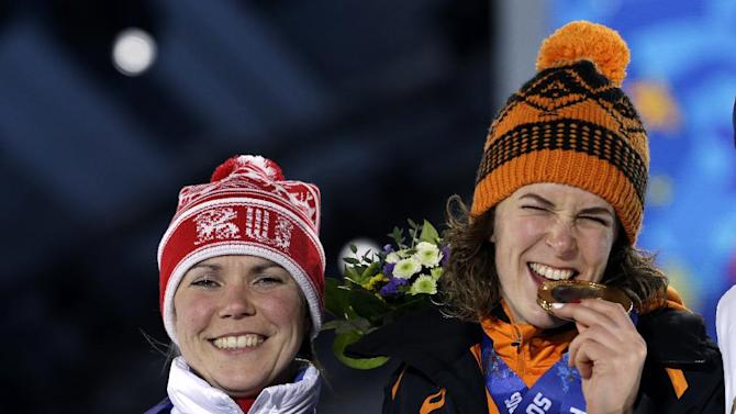 Women's 3,000-meter speedskating bronze medalist Olga Graf of Russia smiles along side gold medalist Irene Wust of the Netherlands during their medals ceremony at the 2014 Winter Olympics in Sochi, Russia, Monday, Feb. 10, 2014