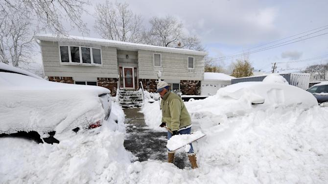 Susan Kelly digs out two cars parked in front of her home on 17th Street after a snow storm on Saturday, Feb. 9, 2013 in Bayville, N.Y. The downstairs of her home was flooded by Superstorm Sandy. The roof blew off and the ceiling collapsed. A storage container in the driveway still holds many household items. A howling storm across the Northeast left the New York-to-Boston corridor shrouded in 1 to 3 feet of snow Saturday, stranding motorists on highways overnight and piling up drifts so high that some homeowners couldn't get their doors open. More than 650,000 homes and businesses were left without electricity. (AP Photo/Kathy Kmonicek)