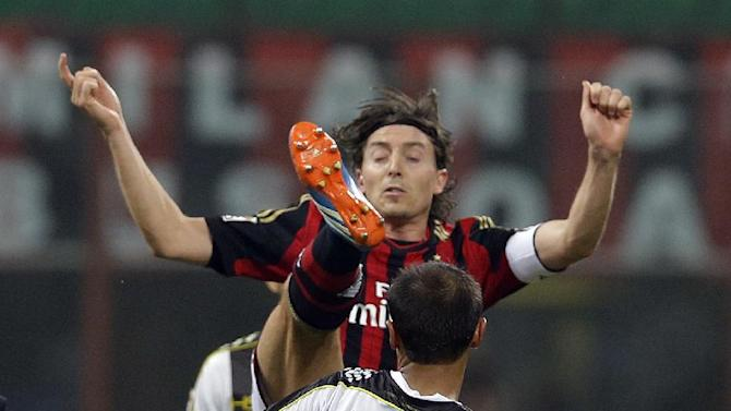 AC Milan's Riccardo Montolivo, top, is challenged by Udinese defender Danilo during a Serie A soccer match between AC Milan and Udinese, at the San Siro stadium in Milan, Italy, Saturday, Oct. 19, 2013